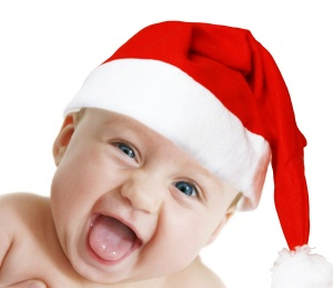 baby in Christmas bonnet looks at camera, on white